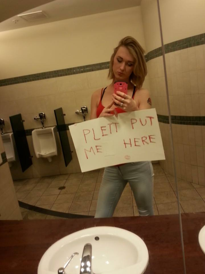 "Brae Carnes in a men's bathroom holding the sign ""Plett put me here."" This would be one of many high-profile protests that would occur as a response to Conservative action to force trans people into the wrong washroom."